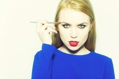 Makeup av den trendiga flickan med den propra framsidan f?r borste royaltyfri fotografi