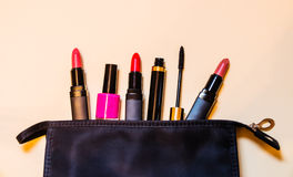 Makeup bag with cosmetic products spilling out to beige background. Black makeup bag with cosmetic products spilling out to beige background Stock Images