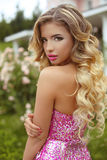 Makeup. Beautiful girl with blond long wavy hair posing in Fashi. On dress, attractive model in blossom park royalty free stock photos