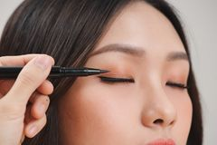 Makeup beauty with brush eye liner on pretty woman face royalty free stock images