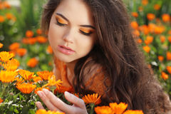 Makeup. Beauty Long Wavy Hair. Beautiful Brunette Woman over mar. Igold flowers. Healthy Hairstyle. Outdoors portrait Stock Images