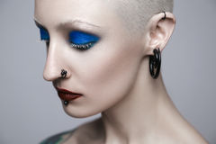 Makeup and beauty topic: punk girl with blue eyes and red lips on gray background in studio Stock Photos