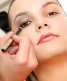 Makeup and beauty treatment. Close up of a beautician creating makeup for a client Stock Image