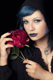Makeup blue hair woman with black hood cap and rose. A young woman wearing makeup and with a black hood holding a red rose in her hand. She has her hair blue Royalty Free Stock Photography