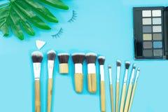 Makeup borstar, dagliga sminkhjälpmedel på blått royaltyfri bild