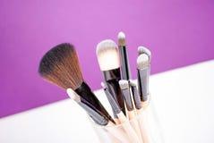 Makeup borstar tätt upp på purpurfärgad bakgrund Arkivbild