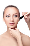 Makeup for brunettes. The makeup artist applied with a Foundation brush on the face. perfect skin women. makeup for brunettes Stock Photos