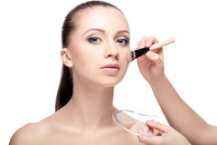 Makeup for brunettes. The makeup artist applied with a Foundation brush on the face. perfect skin women. makeup for brunettes Royalty Free Stock Image