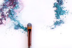 Makeup brush background with eyeshadow sprinkled on white Stock Images