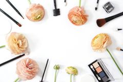 Makeup brush collection eye shadow and ranunculus flowers isolated on white background. Photo royalty free stock photo
