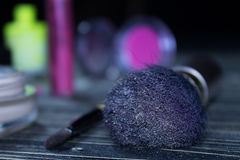 Makeup brush and cosmetics on wooden table and black background behind, beautiful bokeh. Makeup brush and cosmetics - concealer, blush, lipstick on wooden table Royalty Free Stock Photography