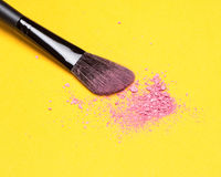 Makeup brush with crushed shimmer blush pink color. Close-up of makeup brush with crushed shimmer blush pink color on bright yellow background Royalty Free Stock Images