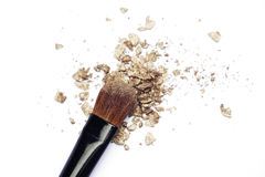 Makeup brush with gold eyeshadows. Makeup brush with broken gold eyeshadows isolated on white Stock Photo