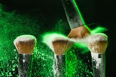 Makeup brush with green mineral powder explosion on black background stock photography