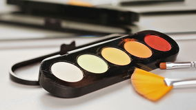 Makeup brush moving over multicolor eye shadows palette stock footage