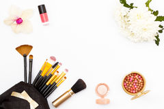 Makeup brush in my purse, nail Polish, flowers, chrysanthemums and orchids and other cosmetics on a white background. Minimal femi. Nine beauty concept. Flat lay Stock Photo