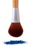 A makeup brush over blue makeup Royalty Free Stock Image