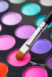 Makeup brush and set of colorful eye shadows Stock Photos