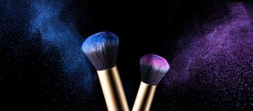 Makeup brush with pink and blue powder explosion Stock Photography