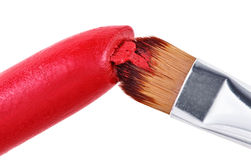 Makeup brush pushed in on red lipstick Royalty Free Stock Photography