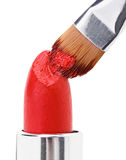 Makeup brush pushed in on red lipstick Stock Photos