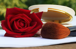 Makeup brush with red rose Stock Photos