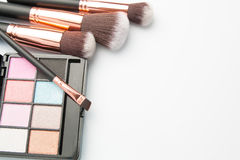 Makeup brush set with eye shadow palette on white Stock Images