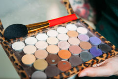 Makeup brush and shadows in hands make-up artist. Close-up Royalty Free Stock Images