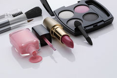 Makeup and brushes. Nail enamel, lipstick, eyeshadow, and cosmetic brushes on white Stock Image