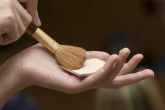 Makeup brushes. Powder on a palm of the young woman Stock Photo