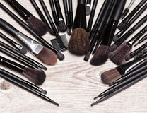 Makeup brushes arranged in semicircle on shabby wooden surface Royalty Free Stock Images