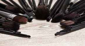 Makeup brushes arranged in semicircle on shabby wooden surface Stock Photo
