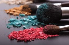 Makeup brushes on background with colorful powder. Stock Photography