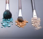 Makeup brushes on background with colorful powder. Stock Photos