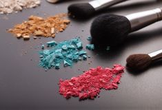 Makeup brushes on background with colorful powder. Royalty Free Stock Image