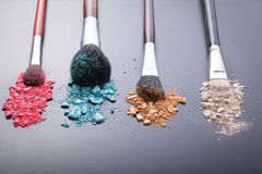 Makeup brushes on background with colorful powder. Royalty Free Stock Images