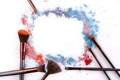 Makeup brushes with blush or eyeshadow of pink, blue and coral tones sprinkled on white background Royalty Free Stock Image