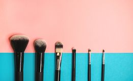 Makeup brushes on colored background. Flat lay. royalty free stock photo