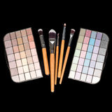 Makeup brushes and colorful make-up eye shadows palette on black background. Fashion woman still life. Makeup brushes and colorful make-up eye shadows palette Stock Photo
