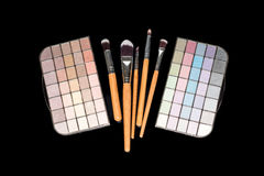 Makeup brushes and colorful make-up eye shadows palette on black background. Fashion woman still life. Makeup brushes and colorful make-up eye shadows palette Royalty Free Stock Photo
