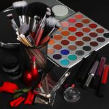 Makeup brushes and cosmetics on a black background royalty free stock photos
