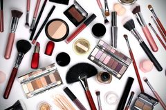 Makeup brushes and cosmetics on a white background royalty free stock photography