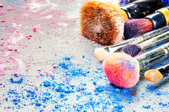Makeup brushes and crushed eyeshadow Stock Photo