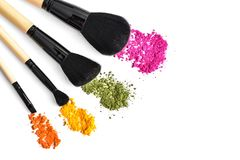 Makeup brushes and crushed eyeshadow Stock Photos