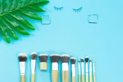 Makeup brushes and earring, everyday make-up tools on blue Royalty Free Stock Photos