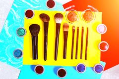 Make-up brushes and eye shadow on colorful background stock photos