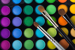 Makeup brushes and eye shadows Stock Photos