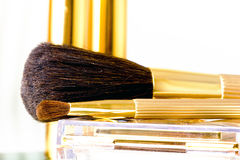 Makeup brushes in gold. Makeup brushes for eyeshadow, blush and powder in golden cover Stock Image