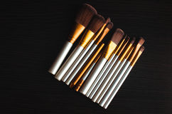 Makeup brushes gold. Makeup brushes on the table wenge dark were gold Stock Image