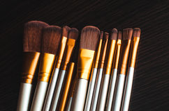 Makeup brushes gold. Makeup brushes on the table wenge dark were gold Stock Photo
